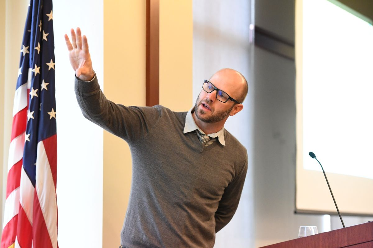 Man wearing a sweater and glasses gestures to something while standing in front of a podium.